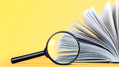 magnifying glass over a book and yellow background behind finding your next role text